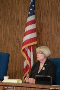 Incumbent Ann Schwab listens intently to a citizen at a council meeting.